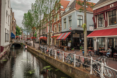 Shopping street with eateries, canal, brick buildings and bicycles on cloudy day in Delft. Calm and graceful village full of canals and Gothic architecture. Stock Photo