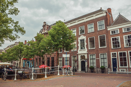 Tree-lined street with bridge, bicycle and facade of elegant brick buildings in Delft. Calm and graceful village full of canals and Gothic architecture. Editorial