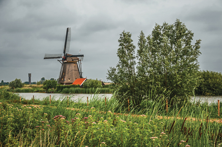 Windmill with house and bushes on the bank of a large canal in a cloudy day at Kinderdijk. Situated in a polder, has the largest concentration of old windmills in the country. Southern Netherlands.