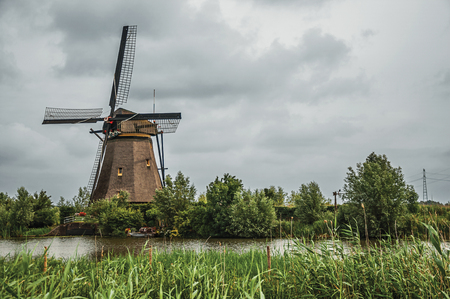 Windmill and tall bushes on the bank of a large canal in a cloudy day at Kinderdijk. Situated in a polder, has the largest concentration of old windmills in the country. Southern Netherlands.