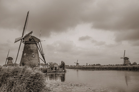 Windmills, bushes and large canal in a cloudy day at Kinderdijk. Situated in a polder, has the largest concentration of old windmills in the country. Southern Netherlands. Black and white photo.