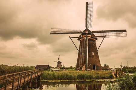 Windmills, bushes and canal in a cloudy day at Kinderdijk. Situated in a polder, has the largest concentration of old windmills in the country. Southern Netherlands. Retro vintage filter. Stock Photo