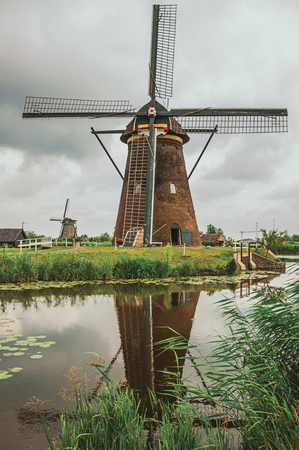 Windmills and bushes on the bank of a large canal in a cloudy day at Kinderdijk. Situated in a polder, has the largest concentration of old windmills in the country. Southern Netherlands. Stock Photo