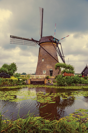 Windmill, bushes and canal in a cloudy day at Kinderdijk. Situated in a polder, has the largest concentration of old windmills in the country. Southern Netherlands. Retro vintage filter.