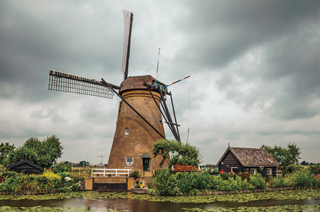 Windmill with house and garden on the bank of a large canal in a cloudy day at Kinderdijk. Situated in a polder, has the largest concentration of old windmills in the country. Southern Netherlands. Stock Photo