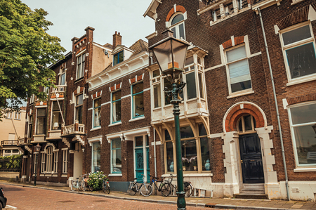 Facade of elegant brick buildings and bicycles on the street in a cloudy day at Dordrecht. Important and historic port city bordered by rivers. Southern Netherlands.