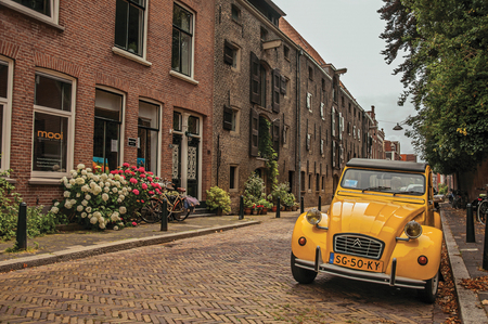 Elegant brick street with typical houses, plant and vintage yellow car in Dordrecht. Important and historic port city bordered by rivers.
