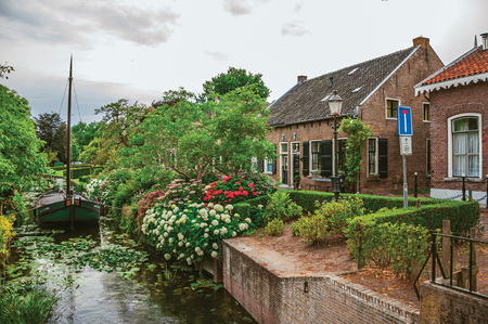 Charming small canal with boat next to a brick rustic house and lush flowery garden in cloudy day at Drimmelen. A lovely small hamlet with harbor and elegance streets. Southern Netherlands.