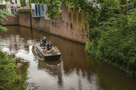 s-Hertogenbosch, southern Netherlands - July 01, 2017. Boat with people navigating the canal surrounded by walls and lush vegetation in s-Hertogenbosch. Historical city with huge cultural life. Editorial