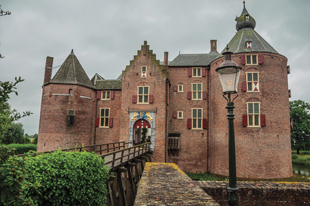 Medieval Ammersoyen Castle with its brick towers, wooden bridge and green garden on cloudy day. Near to the historic and vibrant city of s-Hertogenbosch. Southern Netherlands