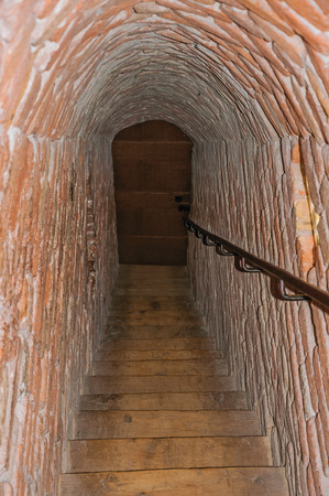 Ammersoyen, southern Netherlands - July 01, 2017. Narrow passage of bricks with stairs inside the walls of the medieval Ammersoyen Castle. Near the historic and vibrant city of s-Hertogenbosch.