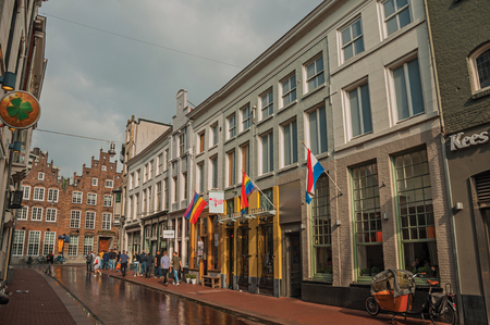 s-Hertogenbosch, southern Netherlands - July 01, 2017. Street with pubs, rainbow flag and people strolling on cloudy day in s-Hertogenbosch. Gracious historical city with vibrant cultural life.