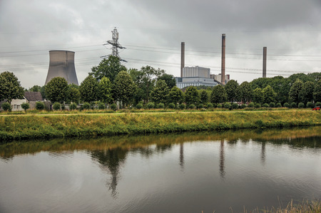 View of canal and gardens with nuclear power plant in background on cloudy day, near the village of Geertruidenberg. A small, friendly place near Aakvlaai Park and Breda. Southern Netherlands. Stock Photo