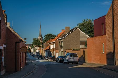 Straße mit Backsteinhäusern bei Sonnenuntergang und blauem Himmel in Tielt. Charmantes und ruhiges Dorf auf dem Land, in der Nähe von Gent und umgeben von landwirtschaftlichen Feldern. Westbelgien.