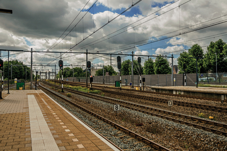 Platform, railroad rails and signaling at train station under blue cloudy sky at Weesp. Quiet and pleasant village full of canals and green near Amsterdam. Northern Netherlands.