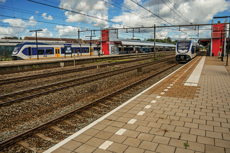 Weesp, northern Netherlands - June 26, 2017. Locomotives stop on train stations platforms, railroad rails and cloudy sky at Weesp. Quiet and pleasant village full of canals and green near Amsterdam.