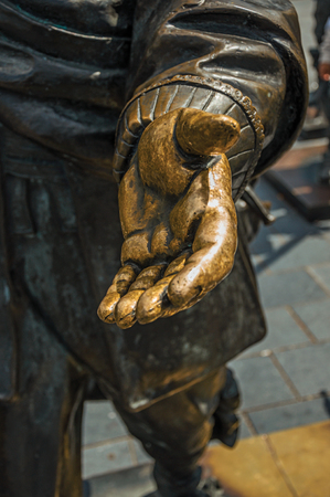 Close-up of open hand in bronze sculpture on the Rembrandt Square in a sunny day at Amsterdam. The city is famous for its huge cultural activity, graceful canals and bridges. Northern Netherlands.