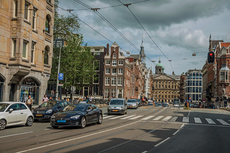 Amsterdam, northern Netherlands - June 26, 2017. Street with old buildings, traffic, people and cyclists passing by in Amsterdam. Famous for its huge cultural activity, graceful canals and bridges. Editorial