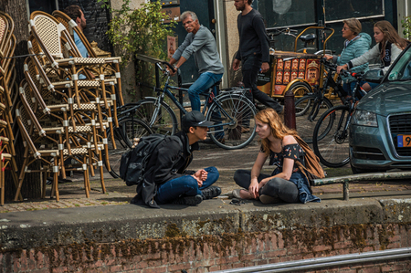 Amsterdam, northern Netherlands - June 26, 2017. Street and young people talking sitting by the canal in a sunny day at Amsterdam. Famous for its huge cultural activity, graceful canals and bridges.