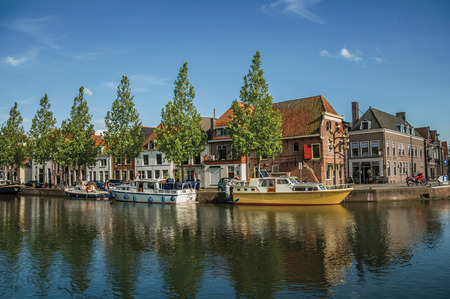 Wide channel with brick houses, boats moored on its bank reflected in water and blue sky of sunset in Weesp. Quiet and pleasant village full of canals and green near Amsterdam. Northern Netherlands.