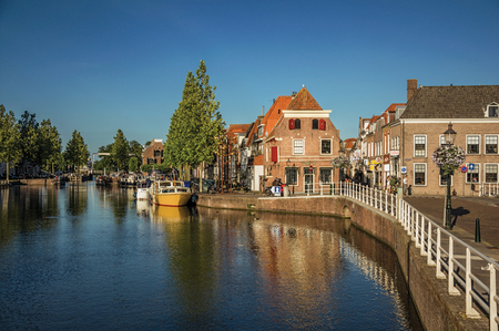 Weesp, northern Netherlands - June 26, 2017. Street and bridge over canal, moored boats and brick houses at sunset in Weesp. Quiet and pleasant village full of canals and green near Amsterdam. Editorial