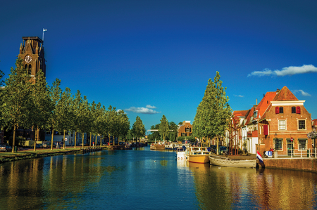 Wide channel with brick houses, moored boats reflected in water and blue sky of sunset in Weesp. Quiet and pleasant village full of canals and green near Amsterdam. Northern Netherlands. Retouched photo Stock Photo