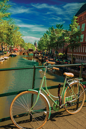 Bridge on canal with bike stuck at balustrade and moored boats under blue sky in Amsterdam. The city is famous for its huge cultural activity and graceful canals. Northern Netherlands. Retouched photo