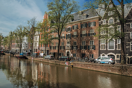 Tree-lined canal with old brick buildings, cars, moored boats and sunny blue sky in Amsterdam. The city is famous for its huge cultural activity, graceful canals and bridges. Northern Netherlands.