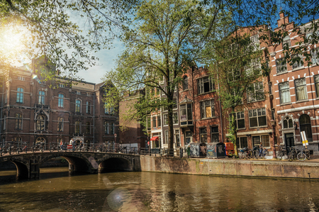 Bridge with iron balustrade on tree-lined canal, old buildings and sunny blue sky in Amsterdam. The city is famous for its huge cultural activity, graceful canals and bridges. Northern Netherlands.