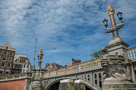 Stone bridge over canal decorated by sculpture of ship's bow and elegant light post in Amsterdam. The city is famous for its huge cultural activity, graceful canals and bridges. Northern Netherlands.