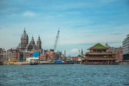 Amsterdam, northern Netherlands - June 27, 2017. Port with ships, church towers and pagoda building in sunny day at Amsterdam. Famous for its huge cultural activity, graceful canals and bridges.