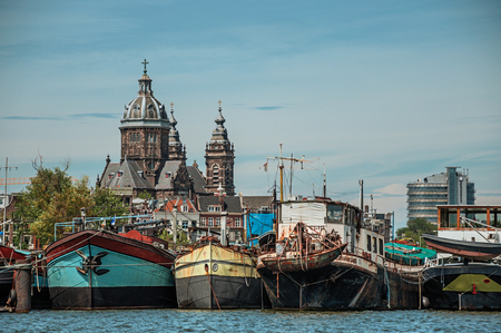Port with rusty moored ships, church towers and building under canal under a sunny blue sky in Amsterdam. Famous for its huge cultural activity, graceful canals and bridges. Northern Netherlands.