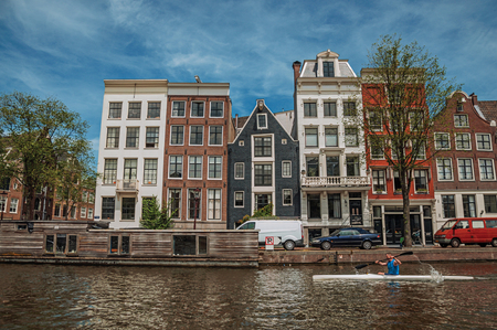 Amsterdam, northern Netherlands - June 27, 2017. Kayak paddler on tree-lined canal with brick buildings and blue sky in Amsterdam. Famous for its huge cultural activity, graceful canals and bridges.