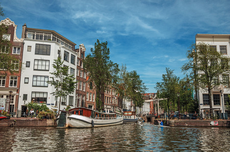 Amsterdam, northern Netherlands - June 27, 2017. Kayak paddler on tree-lined canal with boat, buildings and blue sky in Amsterdam. Famous for its huge cultural activity, graceful canals and bridges.