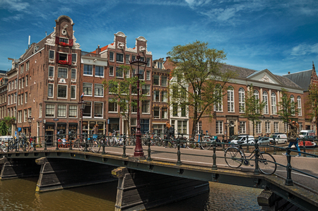 Amsterdam, northern Netherlands - June 27, 2017. Canal with brick buildings, bicycles on bridge and sunny blue sky in Amsterdam. Famous for its huge cultural activity, graceful canals and bridges.