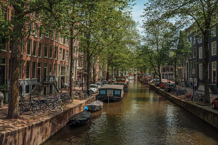 Boats moored at side of tree-lined canal, brick buildings and sunny blue sky in Amsterdam. The city is famous for its huge cultural activity, graceful canals and bridges. Northern Netherlands. Editorial