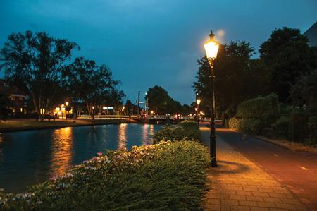Nachtzicht op brede met bomen omzoomde gracht, brug en lantaarnpaal licht op de voorgrond bij dageraad in Weesp. Rustig en gezellig dorp vol grachten en groen nabij Amsterdam. Noord-Nederland.