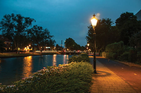 Night view of wide tree-lined canal, bridge and lamp post light in the foreground at dawn in Weesp. Quiet and pleasant village full of canals and green near Amsterdam. Northern Netherlands. Stock Photo