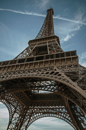 Bottom view of Eiffel Tower made in iron and Art Nouveau style, with sunny blue sky in Paris. Known as the City of Light, it is one of the most impressive cultural centers in the world. Northern France.