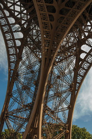 View of one leg's iron structure of the Eiffel Tower, with blue sky and sunshine in Paris. Known as the