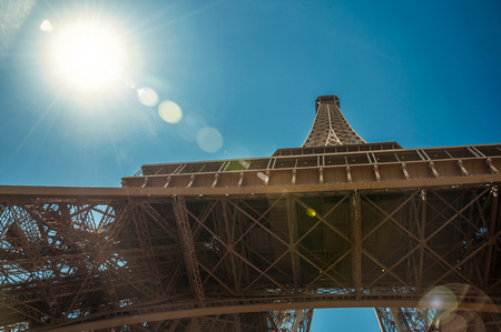 Bottom view of Eiffel Tower made in iron, with sunny blue sky in Paris. Known as the