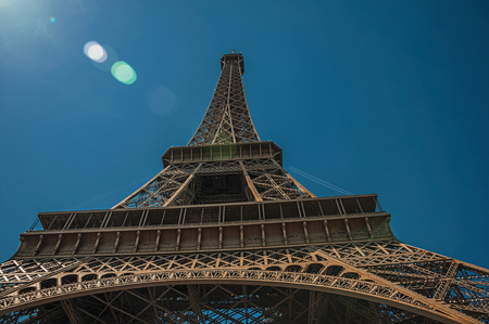 View of the Eiffel Tower all made of iron with blue sky and sunshine in Paris. Known as the