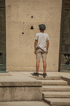 Paris, northern France - July 07, 2017. Boy staring at granite holes on the Human Rights Monument in Paris. Known as the