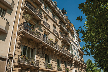 Leafy trees under sunny blue sky and building made in Parisian style of Paris. Known as the City of Light, it is one of the most impressive cultural centers in the world. Northern France. Editorial