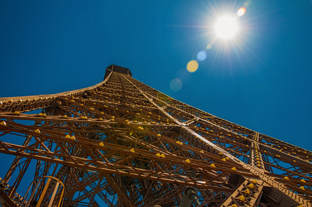 View of the iron structure from the top of Eiffel Tower with sunshine in Paris. Known as the City of Light, it is one of the most impressive cultural centers in the world. Northern France. Retouched photo