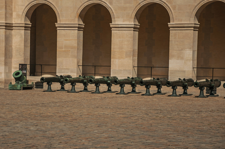 Close-up of the Les Invalides Palace courtyard, with old cannons in the sunny day at Paris. Known as the