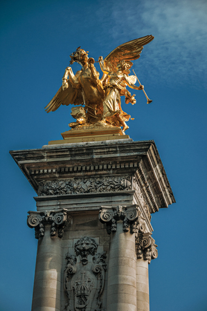 Marble column with golden statue adorning the Alexandre III bridge over the Seine River in Paris. Known as the