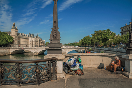 """Paris, France - July 08, 2017. Beggar on bridge over the Seine River with sunny blue sky in Paris. Known as the """"City of Light"""", it is one of the most impressive cultural centers in the world. Northern France. Editorial"""