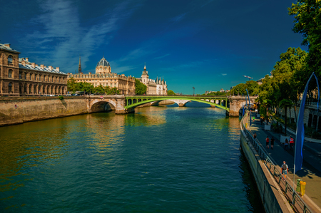 Bridge on the Seine River and the Conciergerie building with blue sky at Paris. Known as the City of Light, it is one of the most impressive cultural centers in the world. Northern France. Retouched photo.