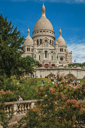 """Paris, France - July 08, 2017. People, trees, domes of the Sacre Coeur Basilica facade in Paris. Known as the """"City of Light"""", it is one of the most impressive cultural centers in the world. Northern France. Imagens"""